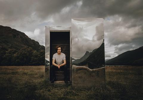 Scott Silven sits on a metallic mirror box in a grassy field with hills in the background and an overcast sky.