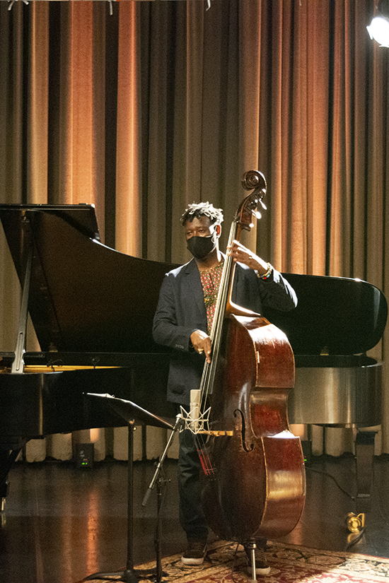 Marcus Shelby stands onstage holding the bass. An empty piano and gold-orange glowing stage curtains are behind him.